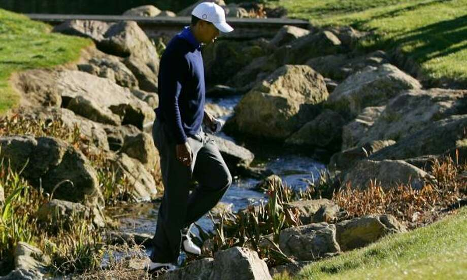 Tiger Woods crosses a creek next to the 18th green as he prepares to take a drop on the way to a double-bogey. Photo: ROBERT LABERGE, GETTY IMAGES
