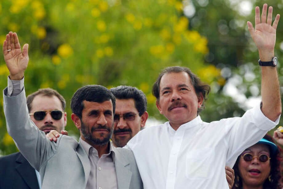 """Iranian President Mahmoud Ahmadinejad and Nicaraguan President Daniel Ortega wave to supporters during a visit to the working-class neighborhood """"Cuba Libre"""" in Managua. Ahmadinejad was on a Latin American tour to round up anti-U.S. allies. He promised closer ties to Nicaragua. Ortega said the visit was """"not merely a matter of protocol."""" Photo: MIGUEL ALVAREZ, AFP/Getty Images"""