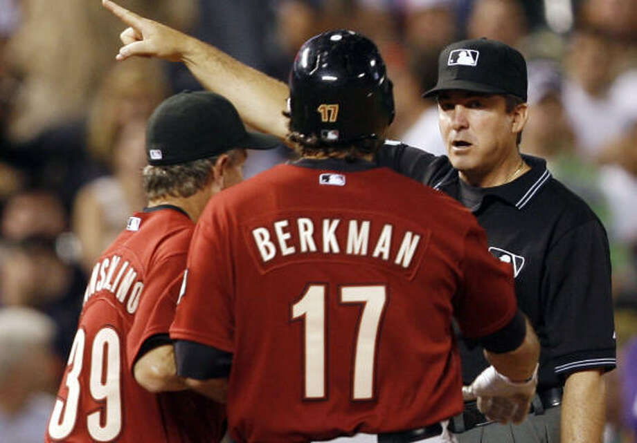 Lance Berkman had to be restrained by Doug Mansolino while arguing with third base umpire Ed Rapuano on Tuesday. Photo: David Zalubowski, AP