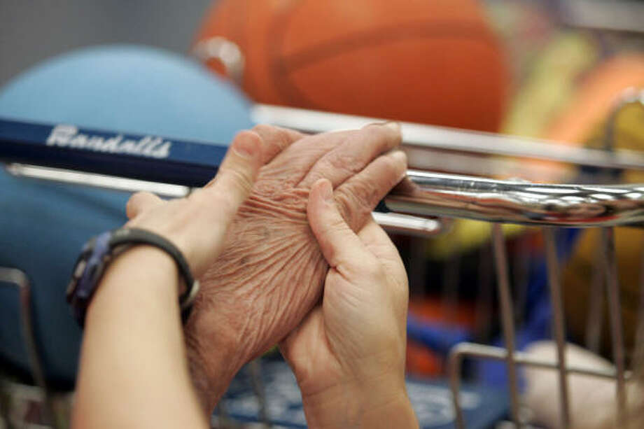 Teresa Cramer helps a patient get his grip. Photo: Johnny Hanson, For The Chronicle