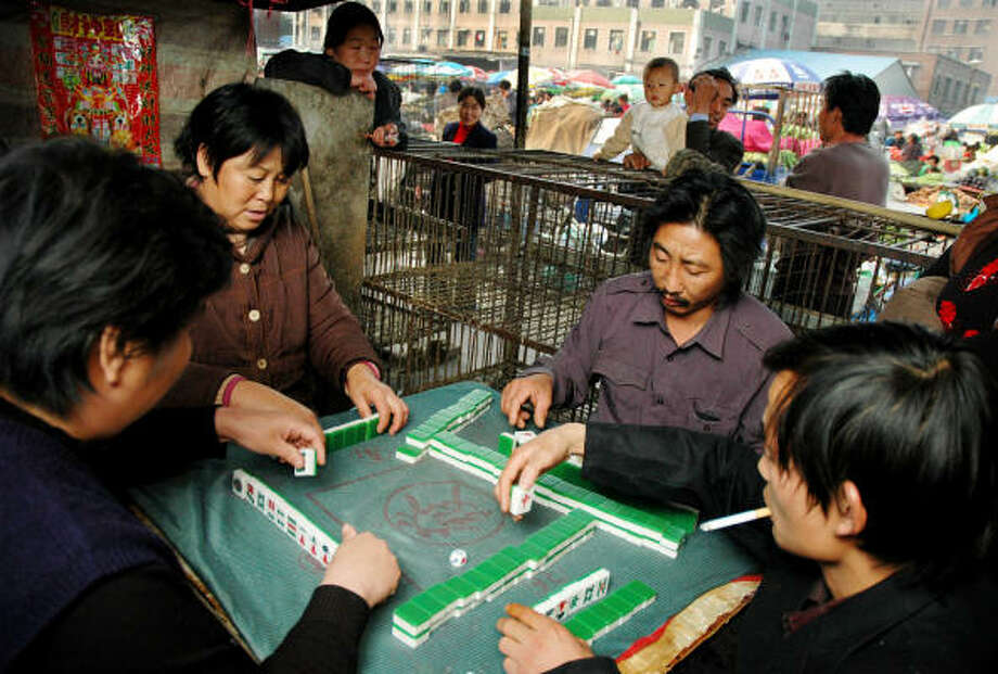 Vendors at a Beijing market play mahjong during a break in 2005. Photo: Associated Press