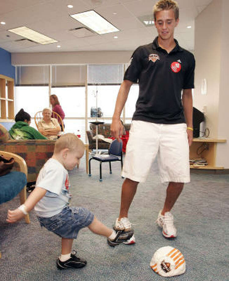 A lobby at Texas Children's Cancer Center and Hematology Service is put to work as a makeshift pitch for Stuart Holden and Martin Echeverria, 3. Photo: Craig Hartley, For The Chronicle