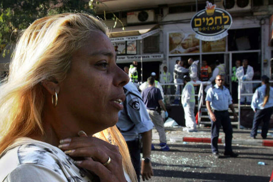 An Israeli woman in shock reacts at the scene of a suicide attack that ripped through the Lehamim Bakery today in the southern Israeli Red Sea resort of Eilat. Three people were killed and one wounded by a Palestinian suicide bomber, the first such attack inside the Jewish state in nine months. Photo: MENAHEM KAHANA, AFP/Getty Images