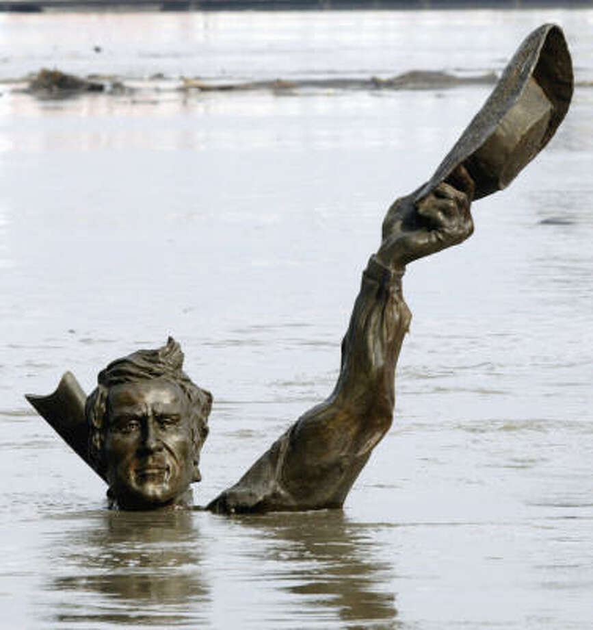 """Part of the submerged statue """"Captains Return"""" appears to be waving from the floodwaters of the Mississippi River as it stands along the riverfront in St. Louis Friday. The floodwaters from the Missouri River are flowing into the Mississippi River causing a rise in the Mississippi River flowing south. Photo: James A. Finley, AP"""