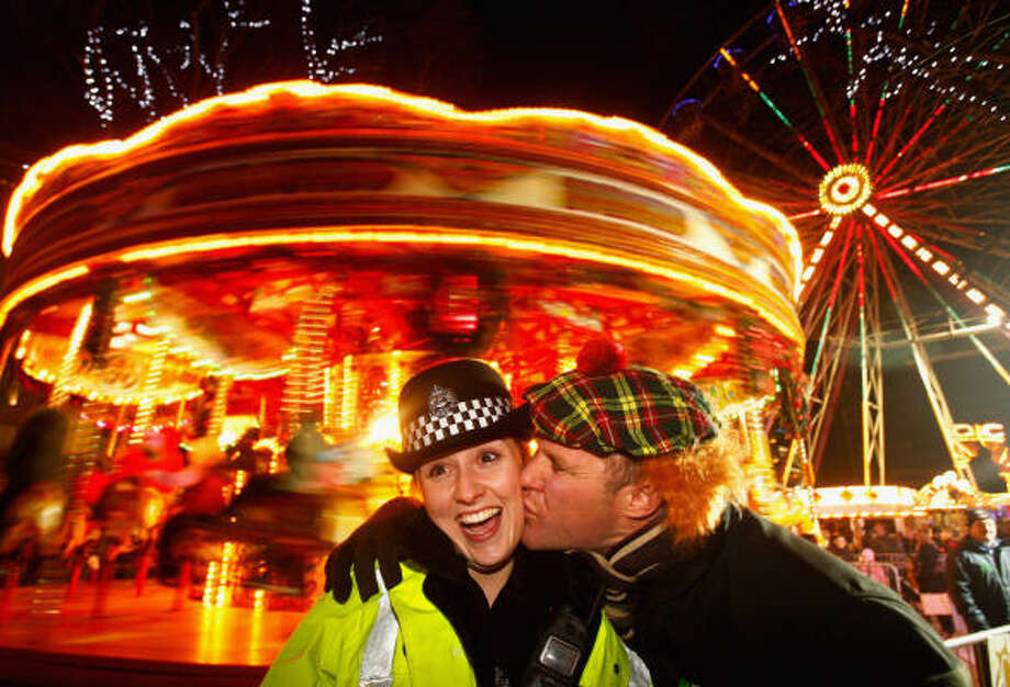 Police constable Lee Dingsdale receives a kiss from Aiden Cooper as revellers take to Princes Street to celebrate New Year in Edinburgh, Scotland. Photo: Jeff J Mitchell, Getty Images