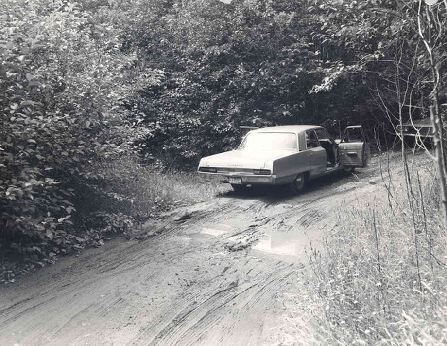 "A King County Sheriff's Office detective's car is seen parked near the site where the remains of ""Tolt Hill Jane Doe"" were discovered on June 5, 1969. Investigators exhumed the woman's remains earlier this month, August 2011, hoping that DNA could help identify the woman and close two cold cases."