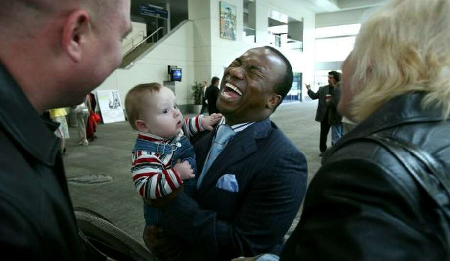 Pastor Sunday Adelaja holds 8-month-old David Rybak while visiting with his parents, Mykhaylo, left, and Oksana Rybak, before a service in Sacramento, Calif. Adelaja, a Nigerian immigrant to Ukraine, says America is becoming a mission ground. Photo: STEVE YEATER, ASSOCIATED PRESS