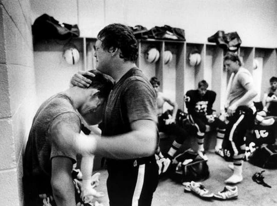 Jerrod McDougal smashes his fist against a concrete wall and hugs teammate Greg Sweat after losing to Midland Lee in an upset in the Odessa Permian Panthers' 1988 football season. Photo: Robert Clark