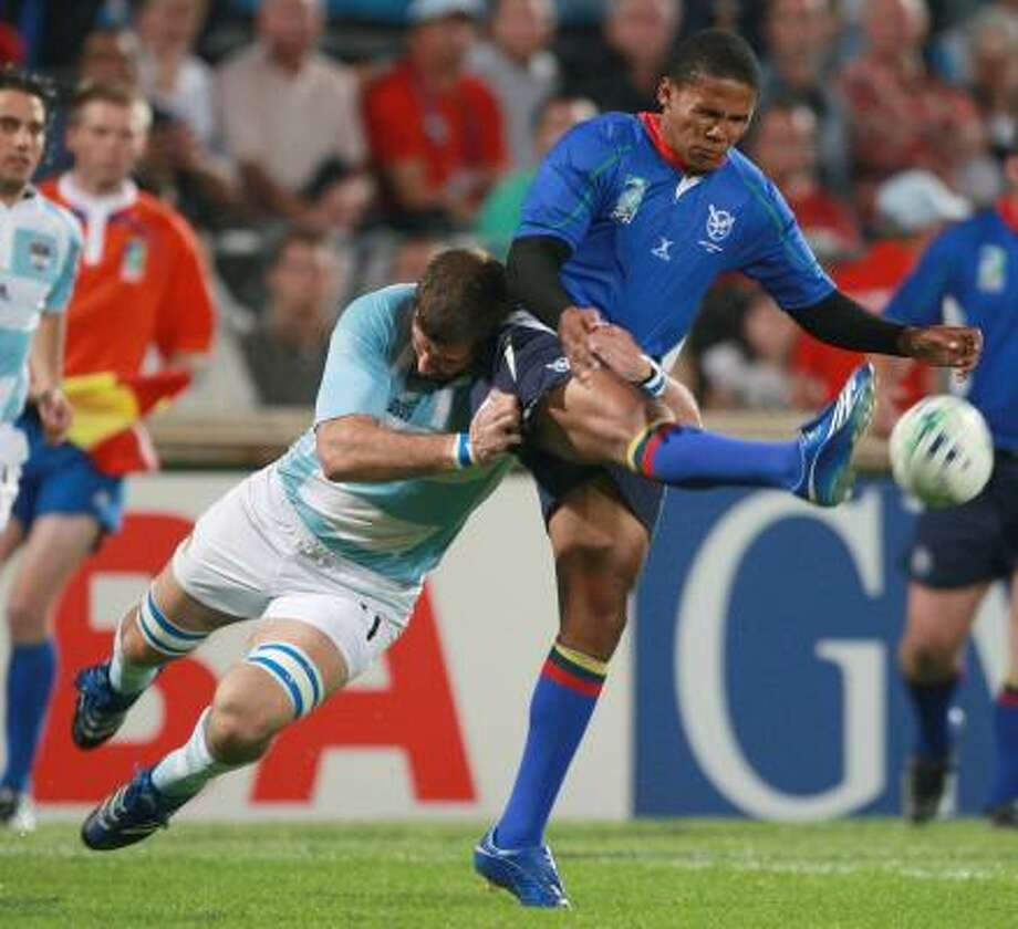 Argentina's Juan Martin Fernandez Lobbe, left, tackles Namibia's Eugene Jantjies in play in the Rugby World Cup on Saturday. Photo: CLAUDE PARIS, ASSOCIATED PRESS