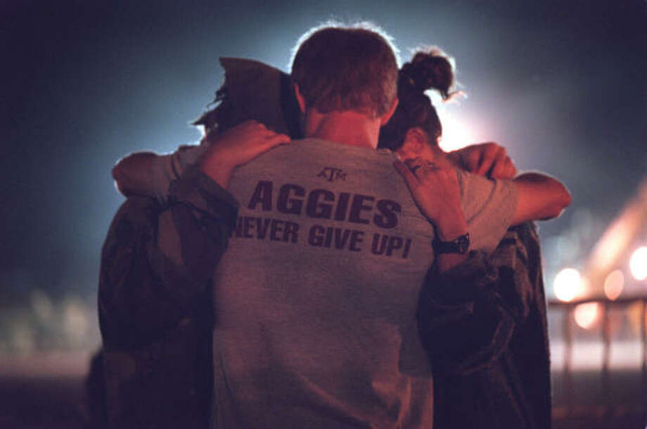Texas A&M students embrace and pray at the site of the collapsed Bonfire in College Station in 1999. In November of that year, the 59-foot-high stack of logs collapsed, killing 12 and injuring 27. Photo: Smiley N. Pool, Chronicle File