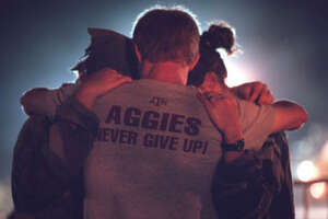 Texas A&M students embrace and pray at the site of the collapsed Bonfire in College Station in 1999. In November of that year, the 59-foot-high stack of logs collapsed, killing 12 and injuring 27.