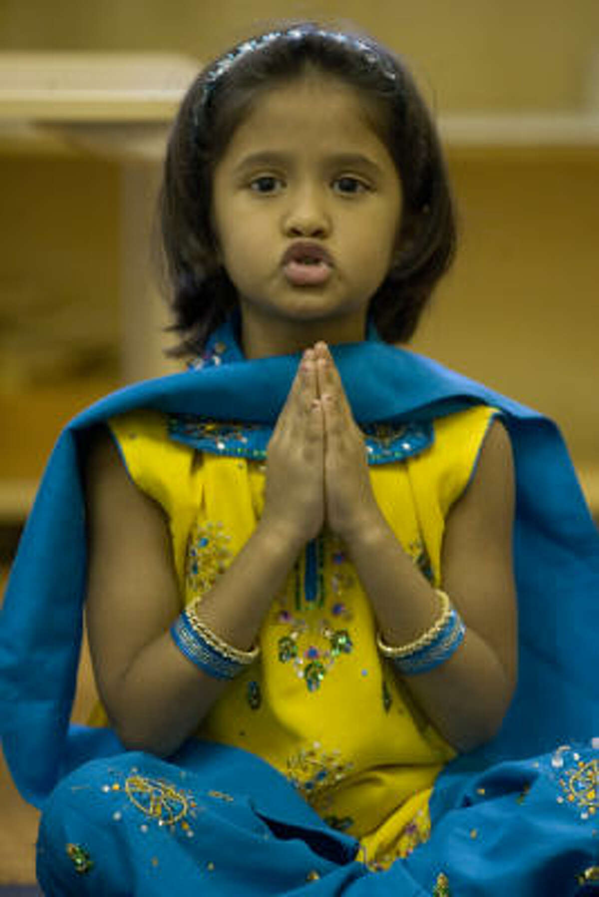 Sakshee Jain says a prayer at Dayanand Arya Vedic Montessori School as her class prepares for the Hindu holiday of Diwali on Wednesday.