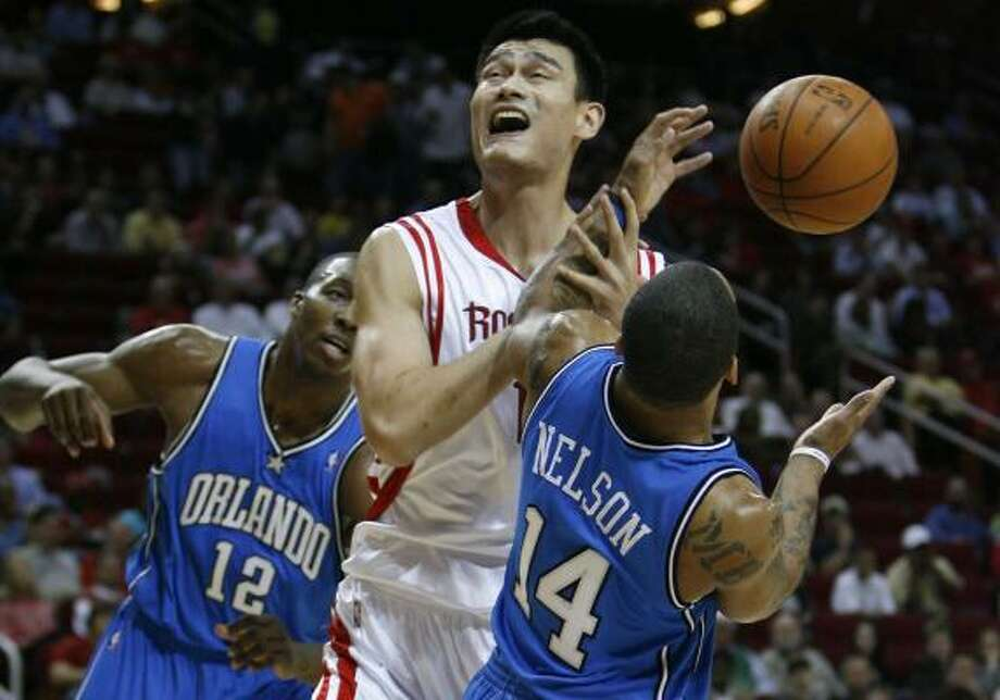Yao Ming finds himself in a tight spot against the Magic's Dwight Howard, left, and Jameer Nelson on Wednesday. Photo: JAMES NIELSEN, CHRONICLE