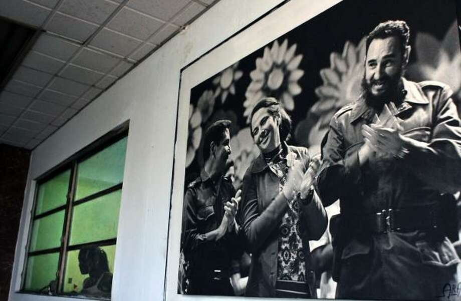 A photo of Cuban leader Fidel Castro, right, his brother Raul Castro and late sister-in-law Vilma Espin decorates the side of an office building in Havana. The ailing Fidel Castro will be replaced by his brother Raul Castro at the regional petroleum summit today in Cuba. Photo: STR, AFP/GETTY IMAGES