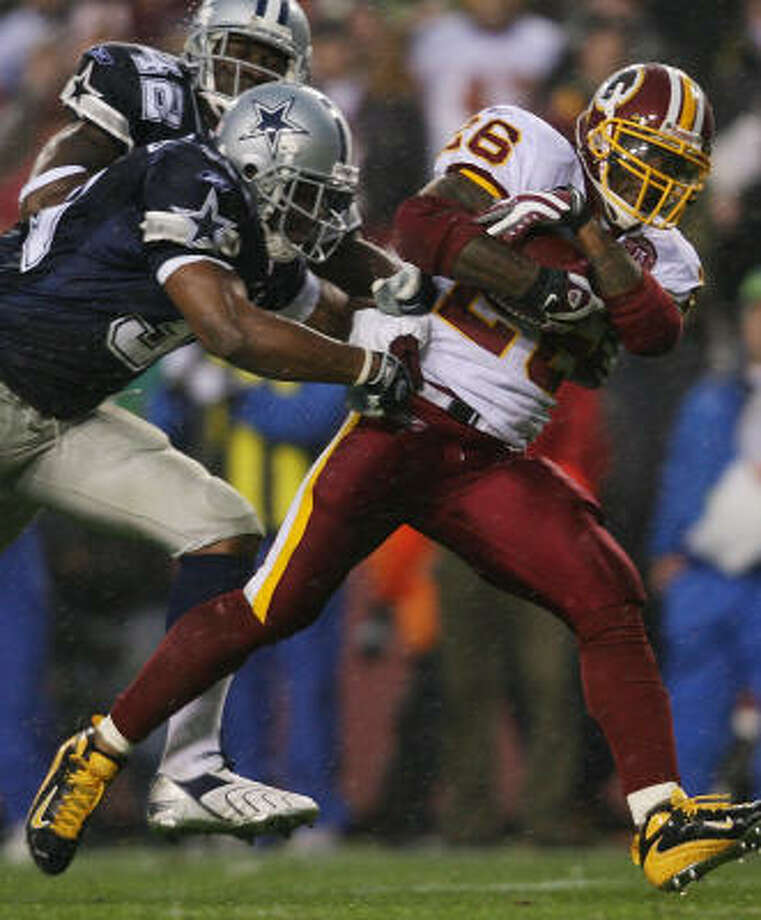 Redskins running back Clinton Portis, right, escapes the Cowboys' Roy Williams, center, and Anthony Henry on his way to scoring one of his two touchdowns in a 27-6 win over Dallas. Photo: Nick Laham, Getty Images