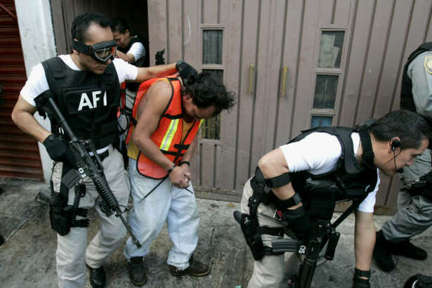 Members of the Federal Investigative Agency escort suspects after a raid in Mexico City on Feb. 9.