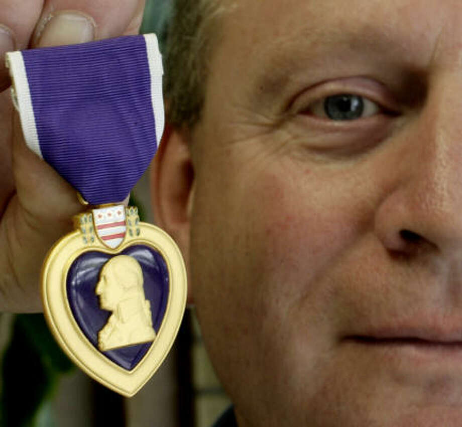 Tom Tucker, owner of Tomball's Graco Awards, holds a revered Purple Heart, Thursday, which was manufactured by his company. Photo: Karen Warren, Chronicle