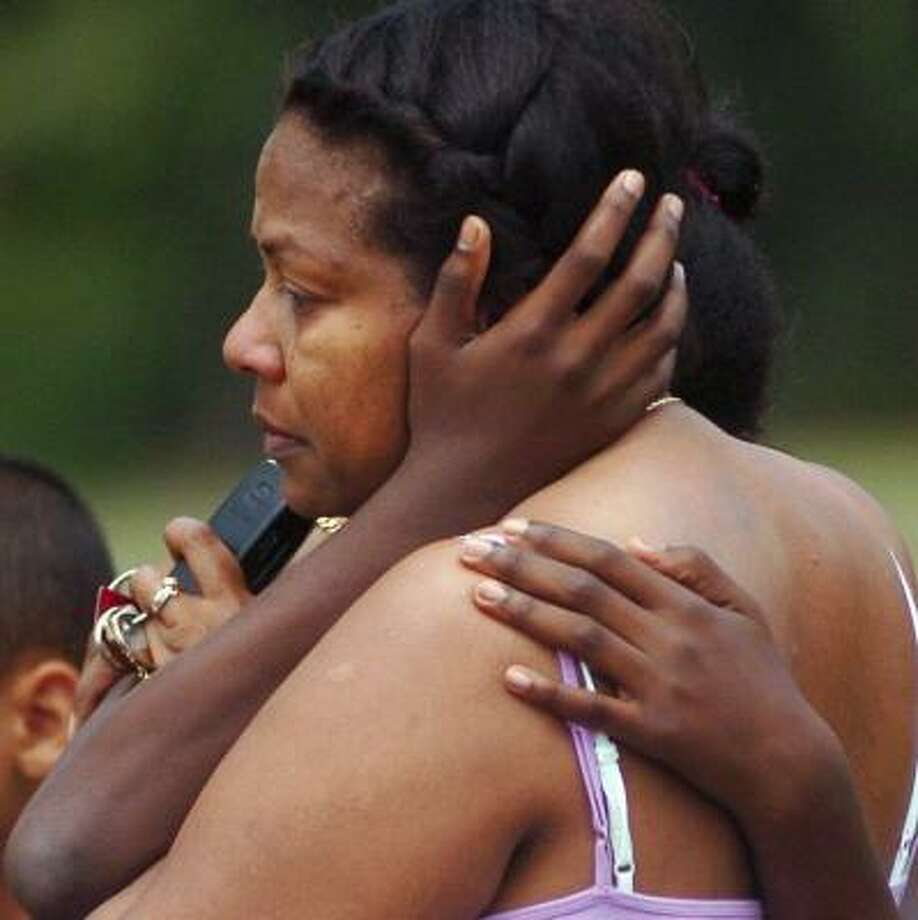 Friends of Michelle McIntosh console one another at a memorial set up near the pond. Photo: WHITNEY KIDDER-ALVAREZ, AP