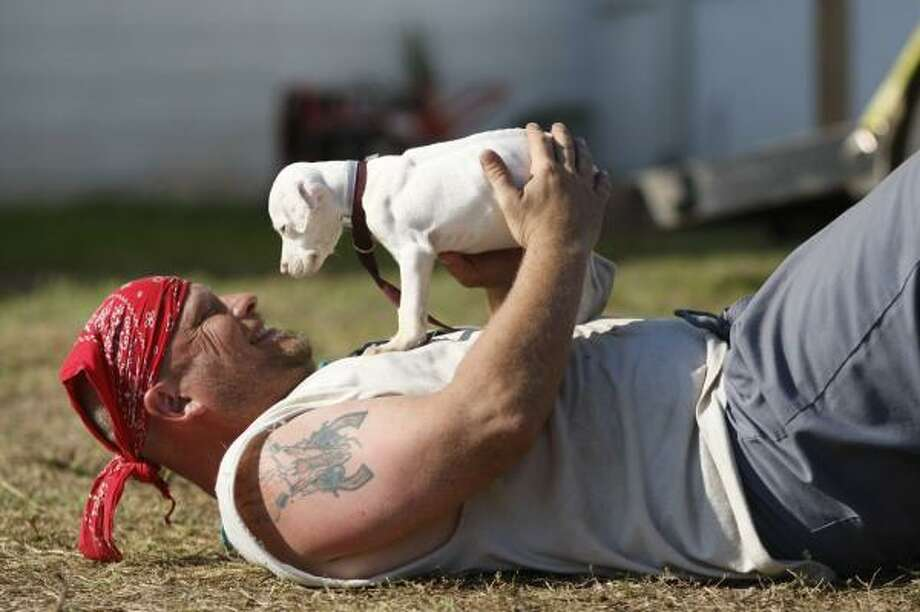 Bryce Lange of Denver, a volunteer for the Houston SPCA's operation in Galveston,  tries to help a displaced puppy relax. Photo: Nick De La Torre, CHRONICLE