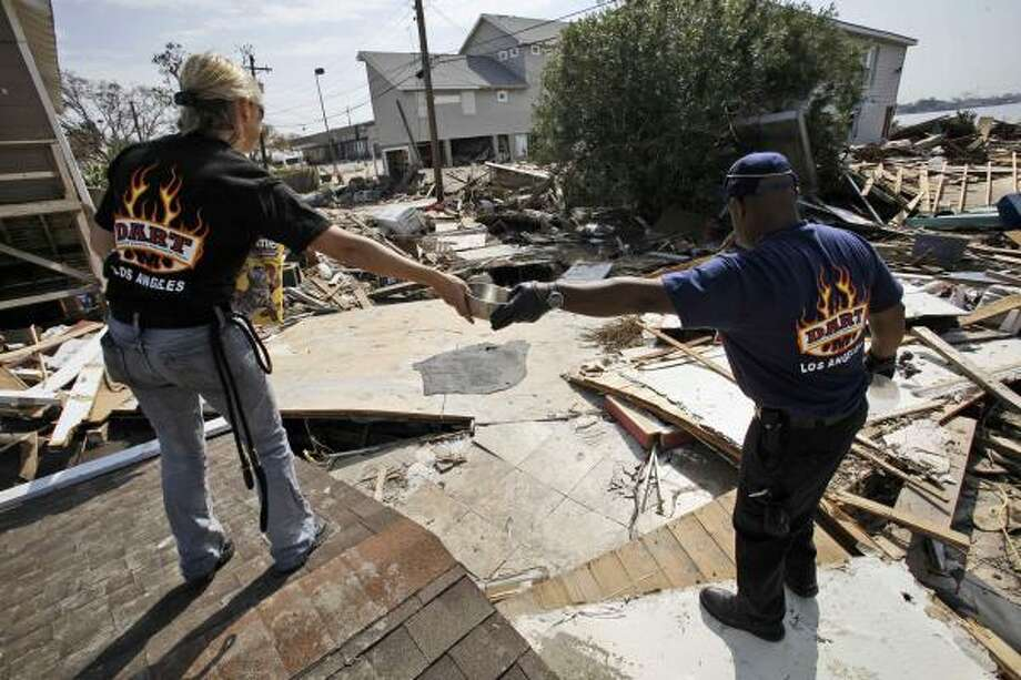 Ernest Coronel, right, hands a bowl to Arlene Hall, both of the SPCA of Los Angeles, in order to put out food and water for displaced pets in Galveston. Photo: LM Otero, AP