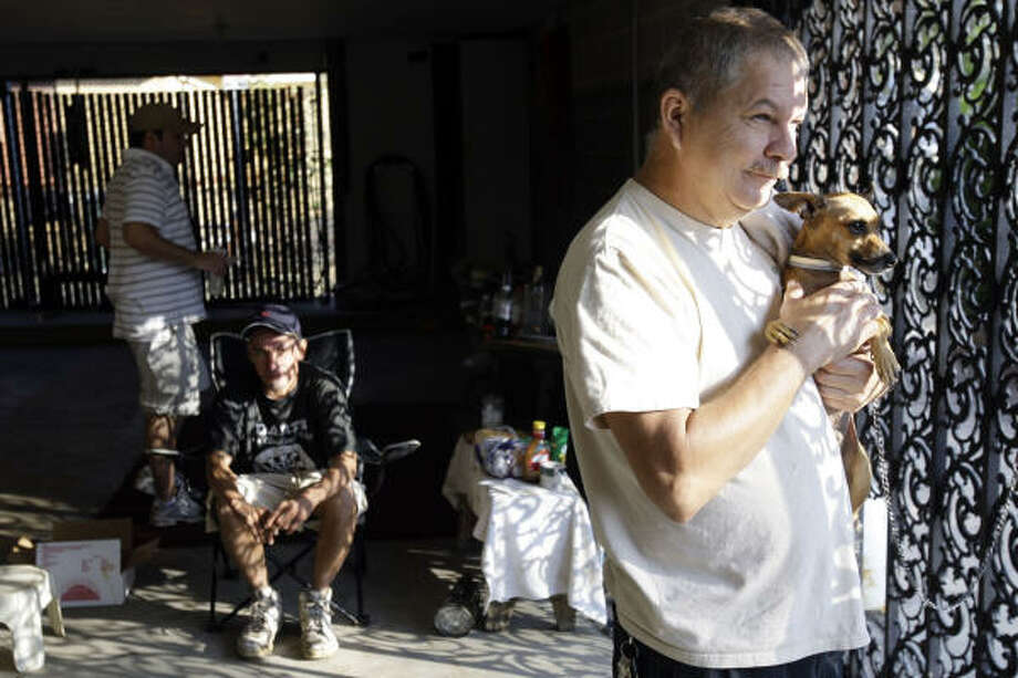 Galveston resident Pete Rodriguez holds a dog he rescued during the hurricane and named Ike. On Wednesday, Rodriguez and others were living out of a garage. Photo: Matt Rourke, AP