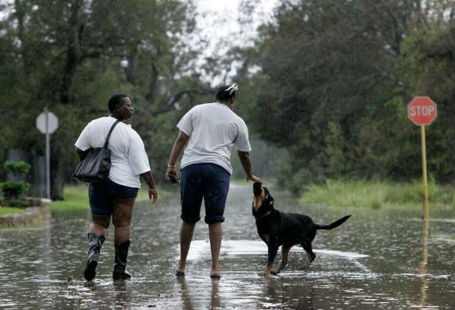 Leesa Berry, left, and Tricia Williams play with a dog that befriended them on Orange's flooded streets. Photo: Tony Gutierrez, AP