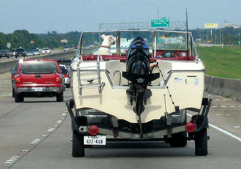 A dog rides in a boat pulled by a pickup on I-10 as Houstonians began heading home after Hurricane Ike. Photo: Laura Weisman, Chronicle