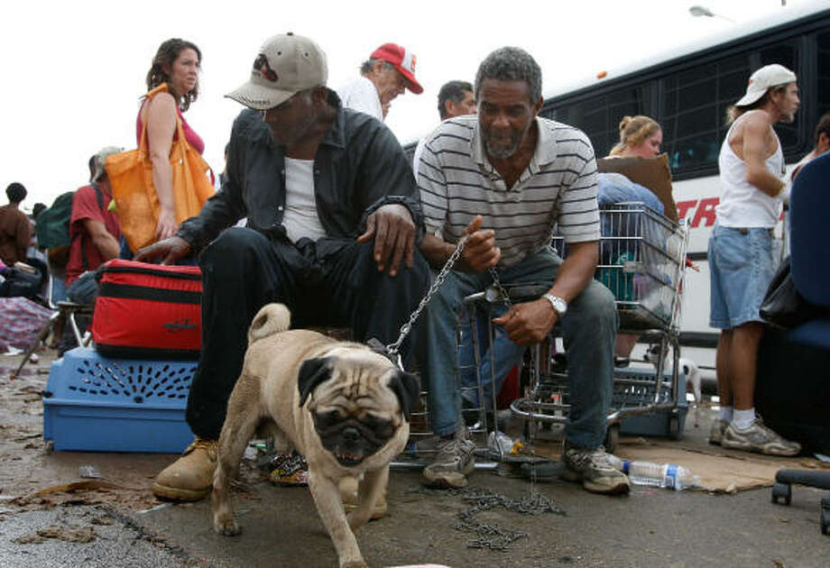 Samuel Stanley, left, and Robert Walker wait with Stanley's dog, Rocky, to be evacuated from Galveston Sunday after their homes were damaged by Ike. Photo: Scott Olson, Getty Images