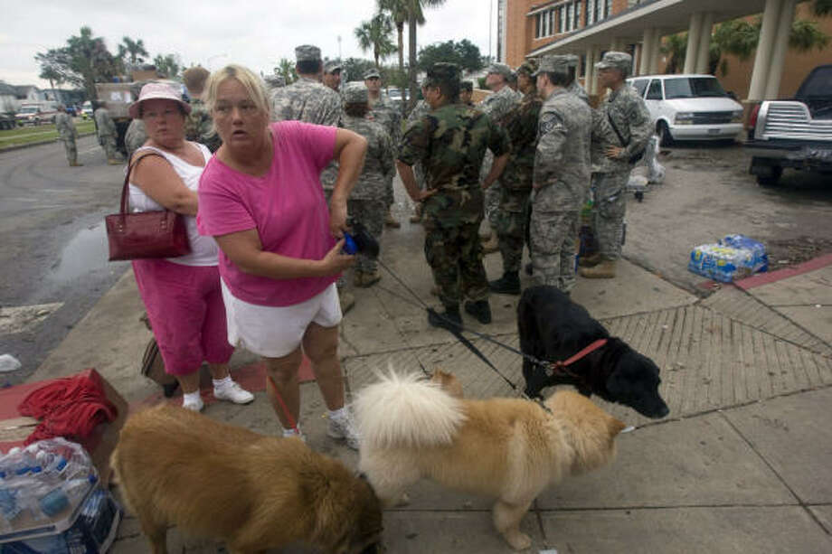 After being stranded at her home in the Pointe West area of Galveston Island's west side after Hurricane Ike, Beth Bishop (left) and her sister Mary Graham and their four dogs are dropped off at a shelter by National Guardsmen Sunday, Sept. 14, 2008. Photo: Johnny Hanson, Chronicle