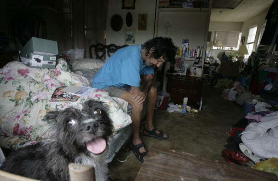 Bill Smith ducked under the radar of police and rode out Hurricane Ike in a Surfside Beach house with his dog Slammer. Smith said he received permission from the house's owner to stay because he didn't have any money or a car to evacuate. Photo: Julio Cortez, Chronicle
