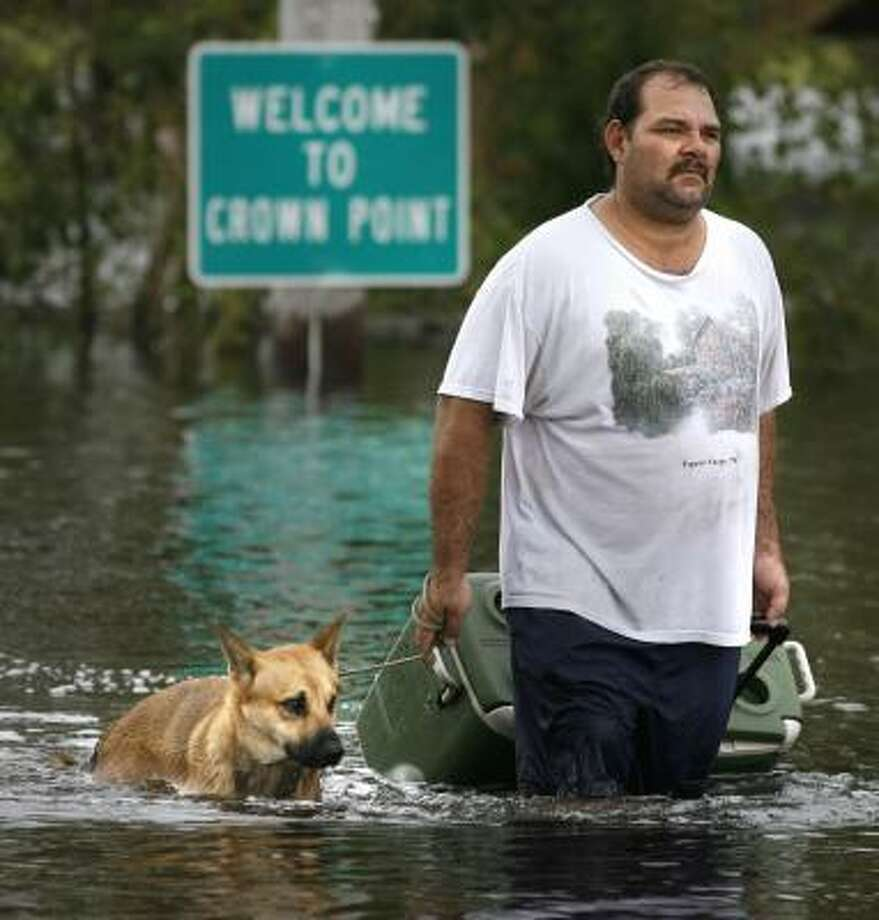 Jeffery Billiot walks through high water from Hurricane Ike's storm surge with his dog Rico after retrieving belongings from his trailer in Crown Point, La., Saturday. Photo: SUSAN POAG, AP