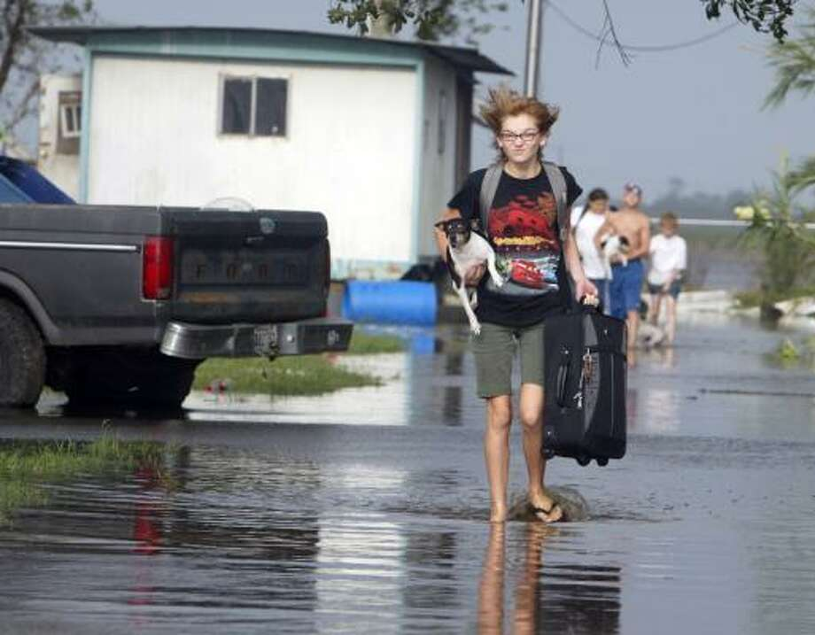 Tristian Miller carries her dog Ozzy and a suitcase as she and her family evacuate their mobile home Saturday in Lydia,  La., which felt Hurricane Ike's storm surge. Photo: John Rowland, AP