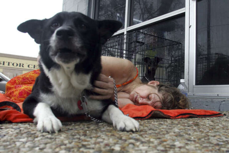 Gail Meads rests with her dog Lucky in front of a shopping center after her home was flooded by hurricane Ike on Galveston's West End. Photo: LM Otero, AP