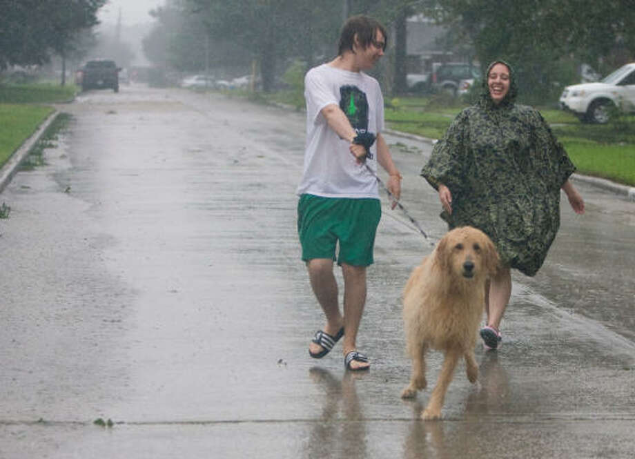 Lane Hullar and his sister Lauren McCarthy take Bunny out for a walk in Spring's Bridgestone West subdivision after the worst of the storm had passed on Saturday. Photo: Steve Campbell, Chronicle