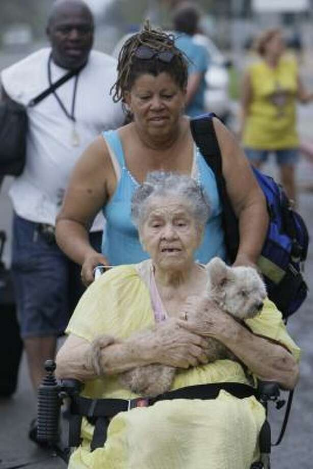 Aletia Skies pushes her mother, Emma Yarborough, and her dog, Pablo, away from a shelter at Galveston's Ball High School Saturday. They were picked up by emergency workers and taken to the shelter but left after deciding conditions were better back at home. Photo: Melissa Phillip, Chronicle