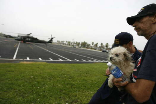 Harlan Willers of Crystal Beach holds his dog Katie after arriving by Texas National Guard UH-60 helicopters at Texas City High School on Saturday. Photo: Sharon Steinmann, Houston Chronicle