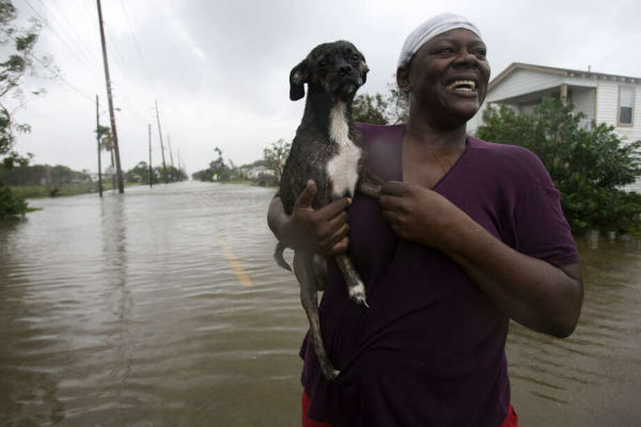 Kim Sexton and her dog, Bullet, survey damage in front of her home on Galveston Island on Saturday. Photo: Johnny Hanson, Chronicle
