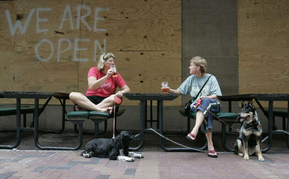 Karen Francis, left, and Sarah Davidson relax with their pets and drink beer Friday outside their downtown Houston residential lofts building. Photo: Pat Sullivan, AP
