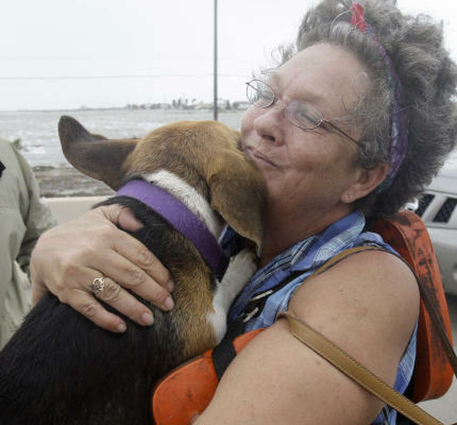 Dondi Fields hugs her dog, Sandy Beach, as Surfside police and firefighters help evacuate the two as well as her husband Friday. Photo: Eric Gay, AP