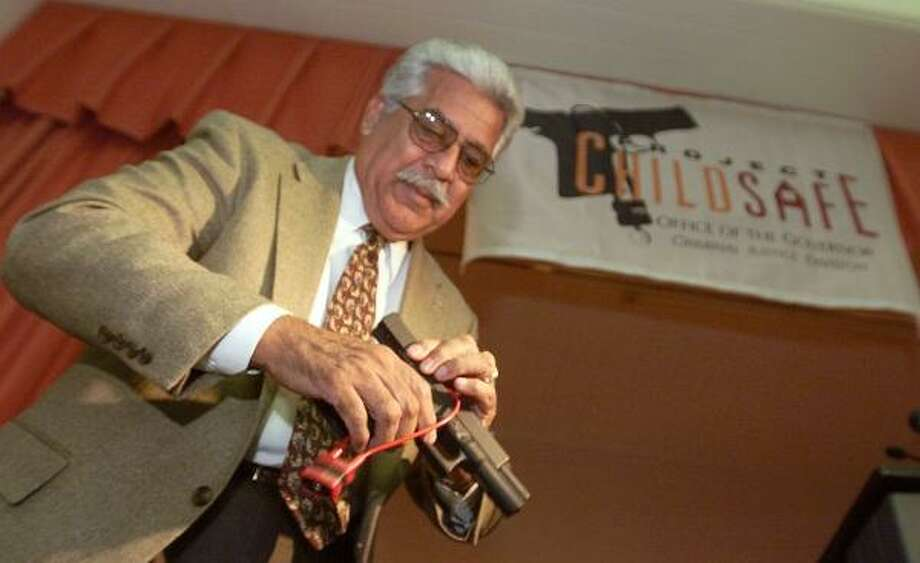 Sheriff Ralph Lopez, shown during a demonstration of a gun lock in 2000, was running for re-election when he resigned. Photo: KIN MAN HUI, San Antonio Express-News