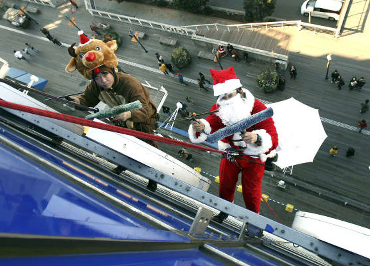 Workers in a Santa Claus and reindeer costume clean an office building's windows in Tokyo on Dec. 23.