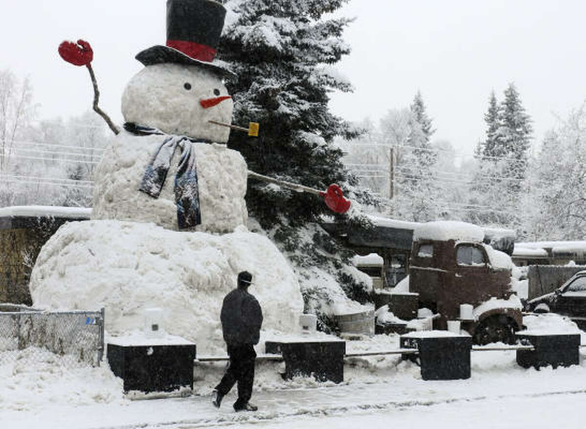 A pedestrian passes a giant snowman on Columbine Street in Anchorage, Alaska, on Dec. 23, 2008. The snowman, known as Snowzilla to many, was completed sometime late Dec. 22 or early Dec. 23, despite city orders that declared the 25-foot snowman a public nuisance.
