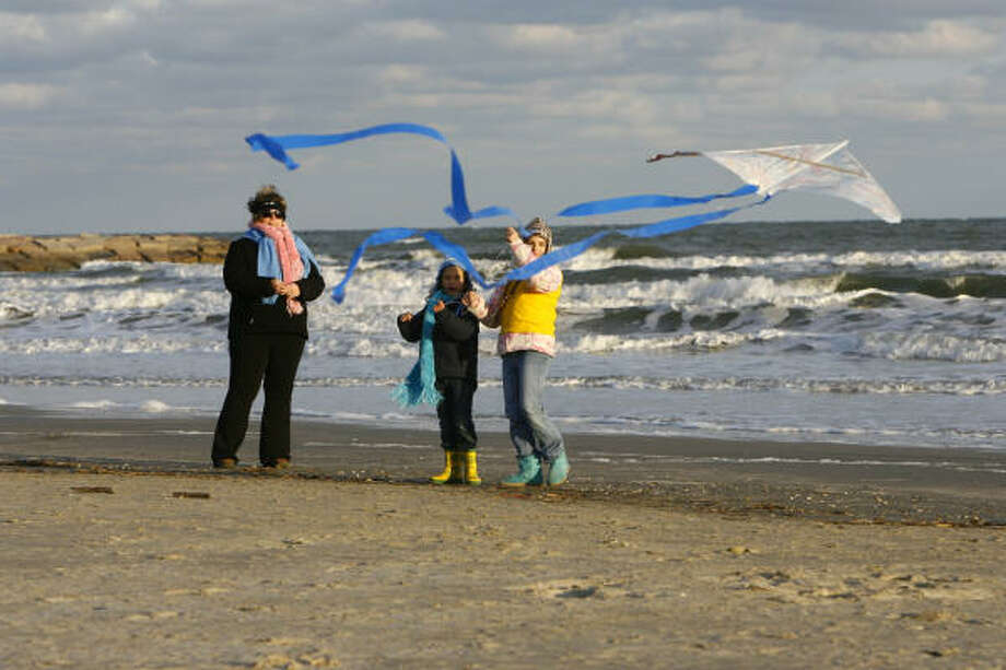 Jan.3 | Sarah Lathrop, 9, front, her sister Rachel Lathrop, 7, and mother Susan Lathrop, all of Montgomery, fly a kite on the beach. | Galveston, Texas Photo: Nick De La Torre, Houston Chronicle