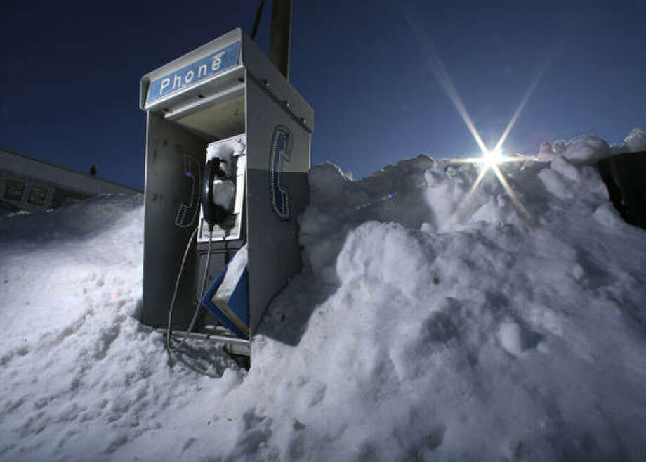 Jan. 3| A pay phone is nearly buried in a snow bank on Main Street. | Winthrop, Maine Photo: Robert F. Bukaty, AP