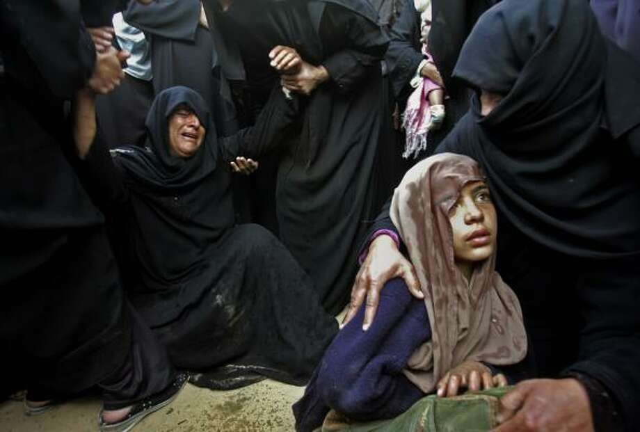 Jan. 3 | The Fayyad family mourns five relatives killed by an Israeli tank shell. | Khan Younis, Gaza Strip Photo: KHALIL HAMRA, AP