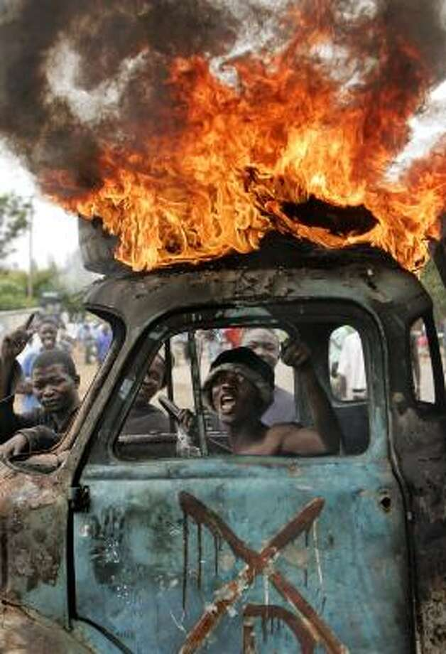 Jan. 29|  A Kenyan man sits in a burning truck used as a makeshift roadblock during an outbreak of violence following presidential elections. Supporters of Raila Odinga accused incumbent President Mwai Kibaki of election fraud. | Kisumu, Kenya Photo: Ben Curtis, AP