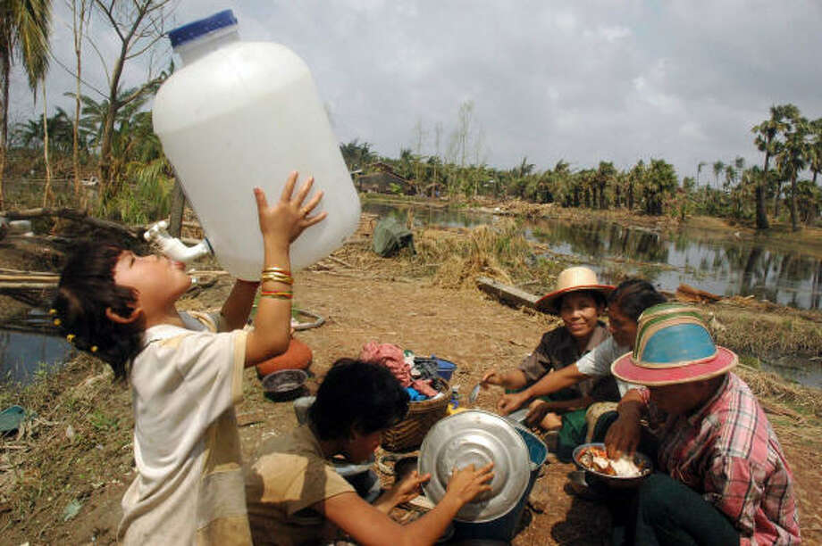 May 7  A girl drinks water from a container as she and her family eat donated food in the outskirts of Yangon after Cyclone Nargis crashed into Myanmar, one of the world's poorest countries, killing more than 22,000 people. The ruling military junta was criticized after delayed aid efforts left thousands vulnerable to a public health crisis.   Konegyangone township, Myanmar Photo: KHIN MAUNG WIN, AFP/Getty Images