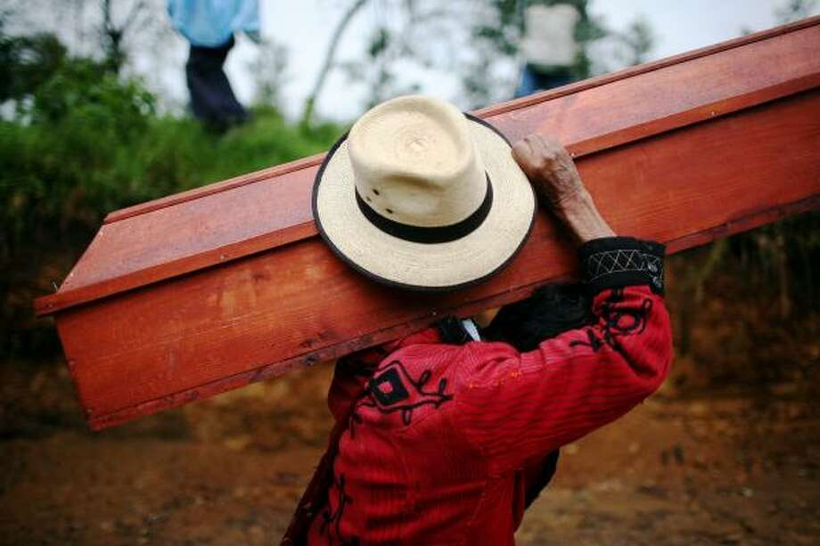 June 10| A man carries the coffin of a victim of the 1981 massacre of 79 people by the Guatemalan Army for a mass burial. | Cocop, Guatemala Photo: Rodrigo Abd, AP