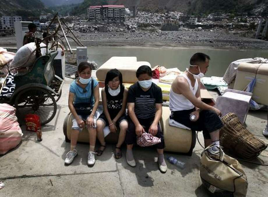 June 24| A family sits on belongings recovered from their earthquake damaged house in Beichuan county. It was the first time families were allowed back to areas devastated by the May 12 magnitude 7.9 earthquake that killed at least 87,000. | Sichuan province, China Photo: Andy Wong, AP