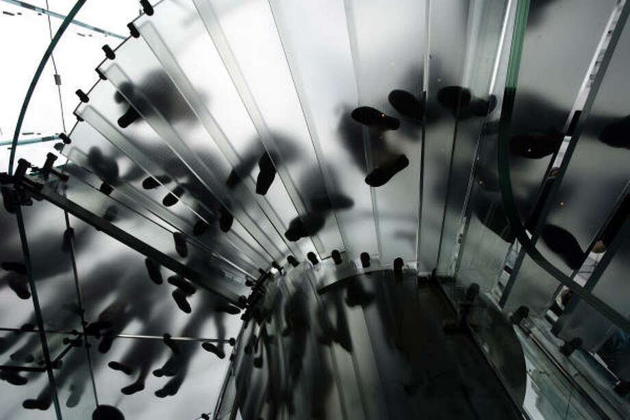 July 9| Customers walk on the glass staircase in New York's Apple store. | New York, New York Photo: Ed Ou, AP